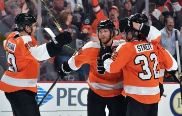 PHILADELPHIA, PA - JANUARY 20: Brayden Schenn #10, Mark Streit #32 and Jakub Voracek #93 of the Philadelphia Flyers congratulate teammate Claude Giroux #28 on his game winning overtime goal against the Pittsburgh Penguins at the Wells Fargo Center on January 20, 2015 in Philadelphia, Pennsylvania. The Flyers won 3-2 in overtime. (Photo by Drew Hallowell/Getty Images)