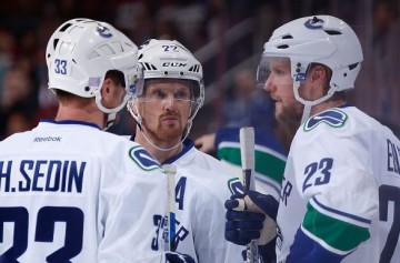 GLENDALE, AZ - OCTOBER 30: Henrik Sedin #33, Daniel Sedin #22 and Alexander Edler #23 of the Vancouver Canucks talk during the NHL game against the Arizona Coyotes at Gila River Arena on October 30, 2015 in Glendale, Arizona. (Photo by Christian Petersen/Getty Images)