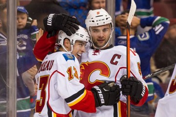 VANCOUVER, BC - OCTOBER 10: Johnny Gaudreau #13 of the Calgary Flames is congratulated by Mark Giordano #5 after scoring the game winning goal in overtime against the Vancouver Canucks in NHL action on October, 10, 2015 at Rogers Arena in Vancouver, British Columbia, Canada. (Photo by Rich Lam/Getty Images)